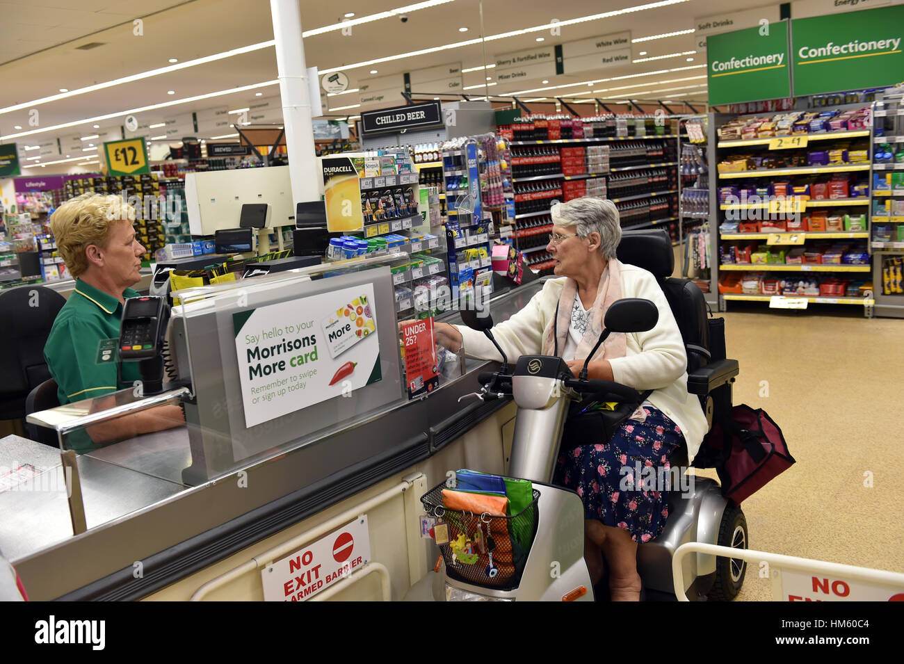A disabled woman is helped at the supermarket checkout with her shopping while using her mobility scooter. - Stock Image