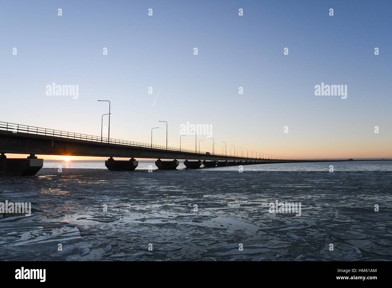 Ice floe and sunset by the Oland bridge connecting the island Oland with mainland Sweden Stock Photo