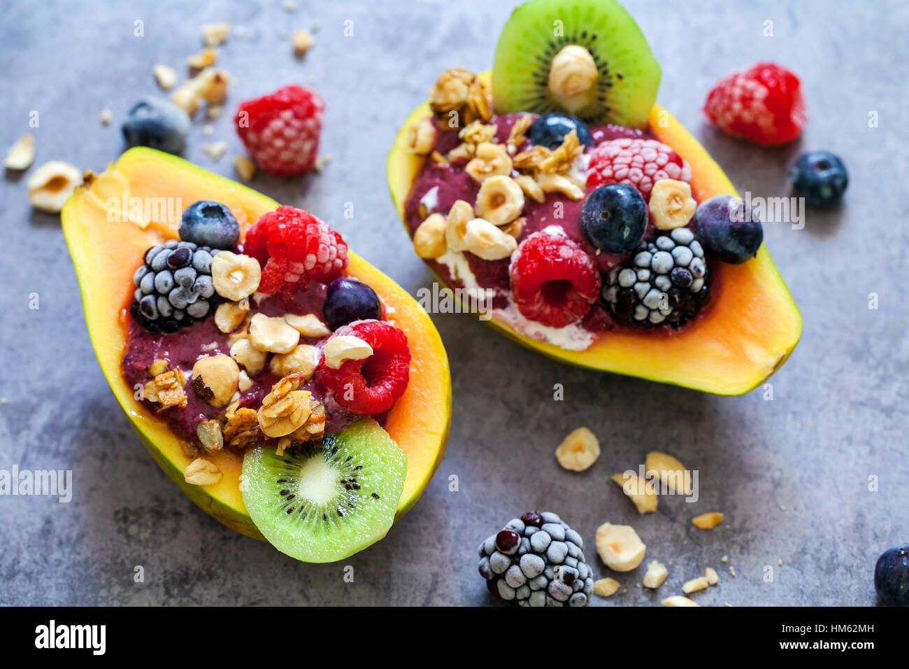 Papaya filled with mixed berry smoothie - Stock Image