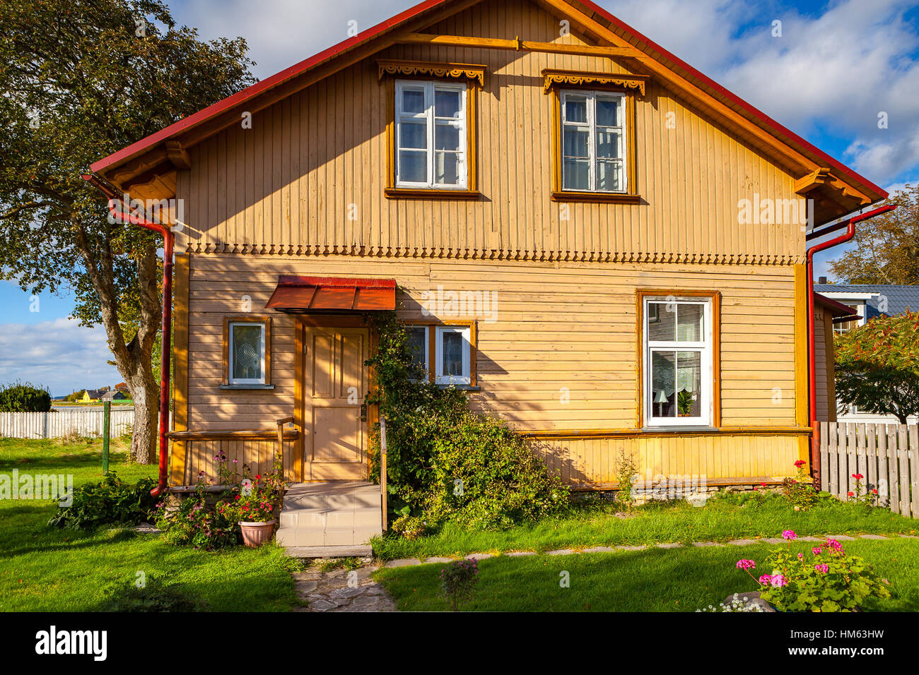 Yellow wooden house with tree and cosy green yard Stock Photo