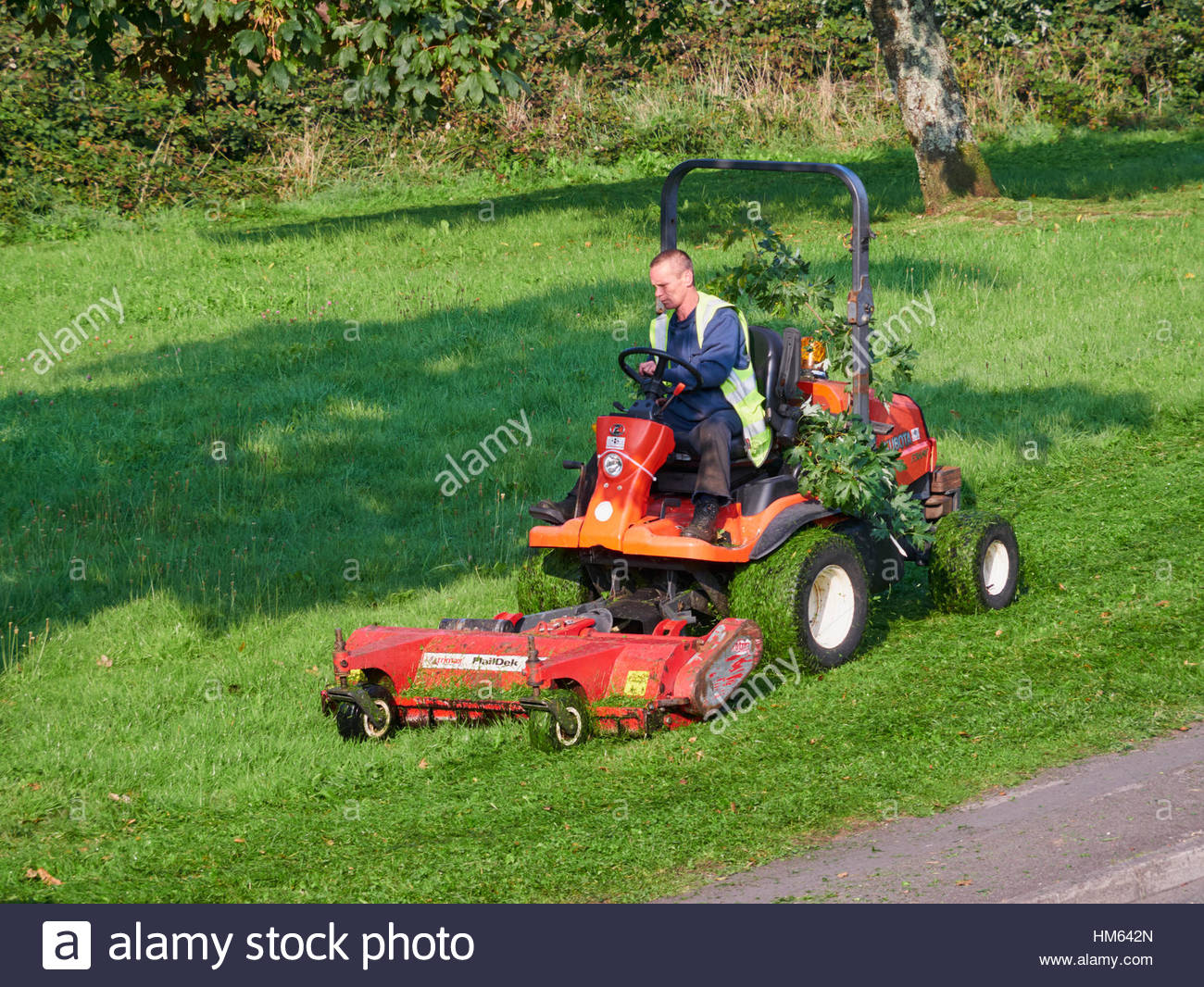 Utility Worker Of For The Local Council With Lawn Mower