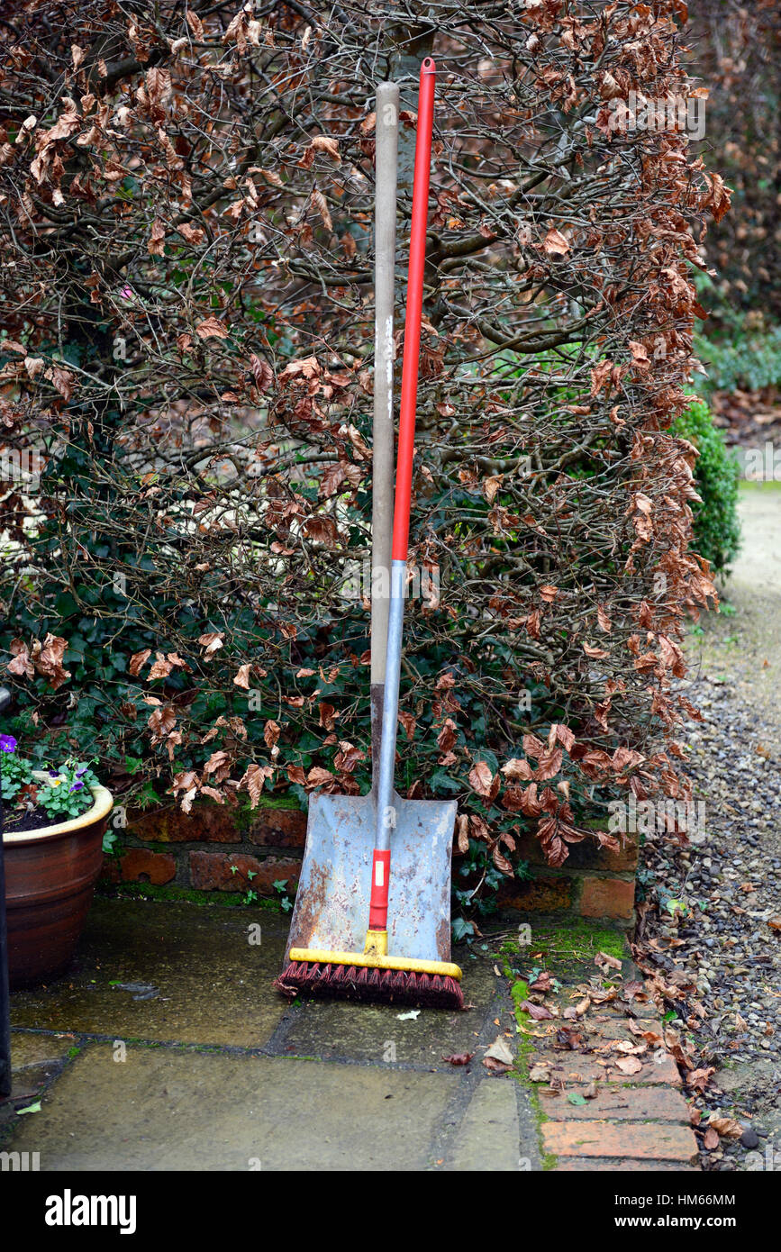 brush and shovel garden tool tools implements tidy tidying stand up against hedge autumn winter gardens gardening - Stock Image
