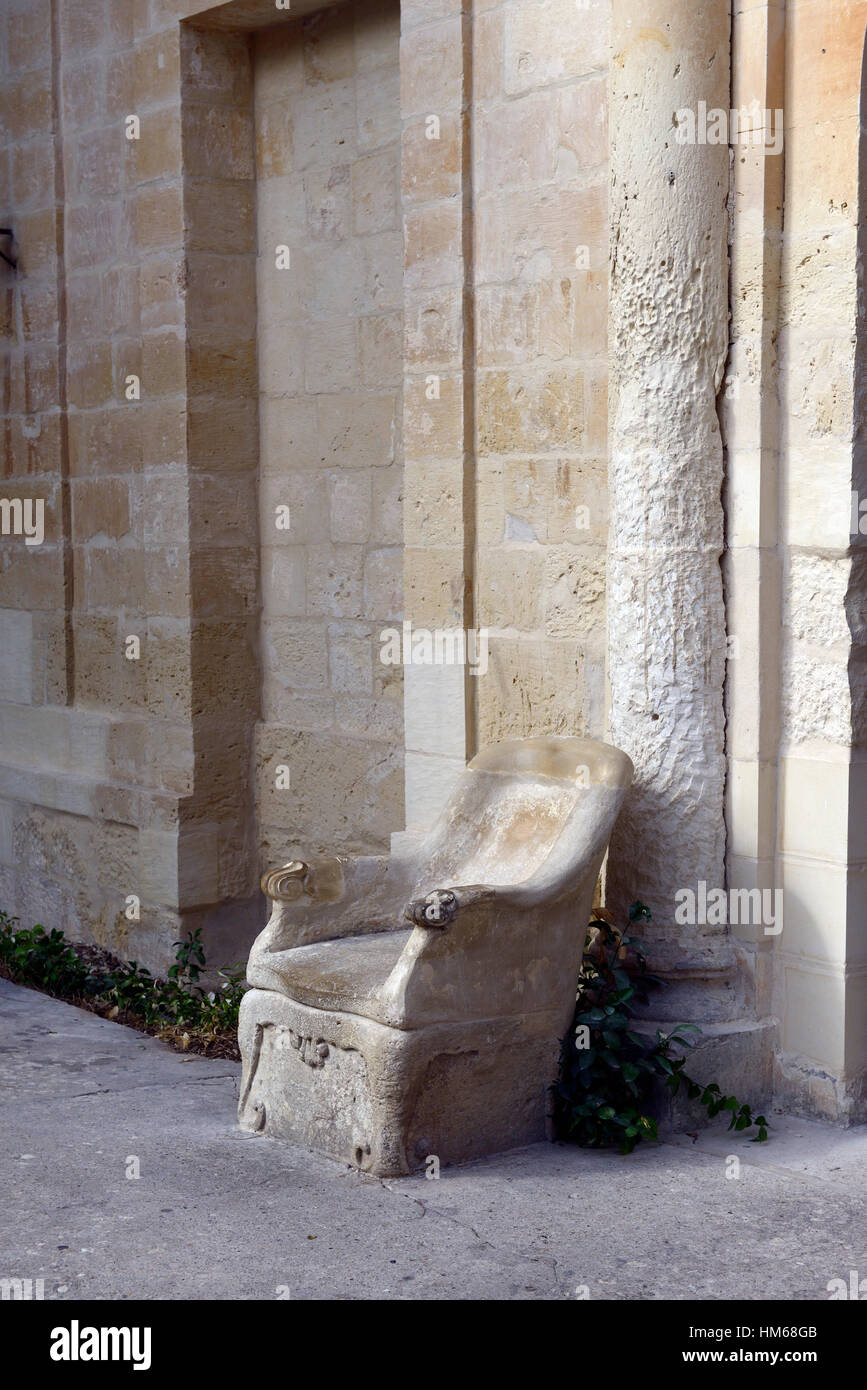carved sculpted sandstone seat chair seating guard guarding entrance Presidential Palace Attard Malta RM World - Stock Image