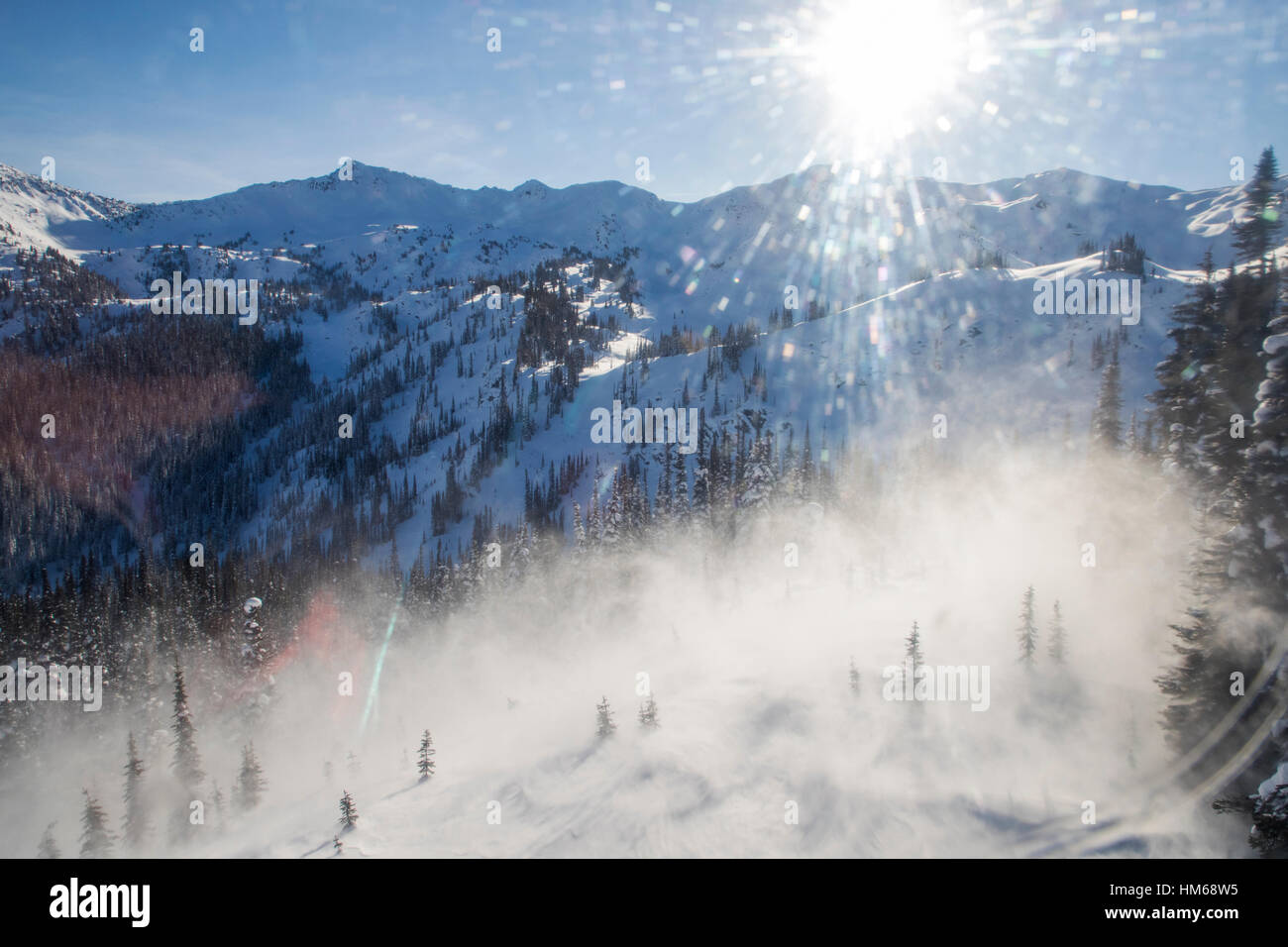 Rotor wash blowing snow from helicopter flying skiers into remote hut; Esplanade Range; sub-range of Selkirk Range; - Stock Image