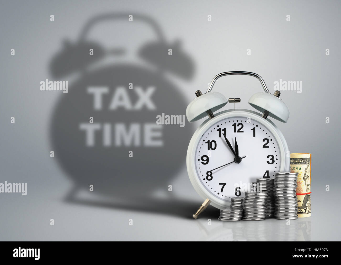 Clock with money and tax time shadow, financial concept - Stock Image