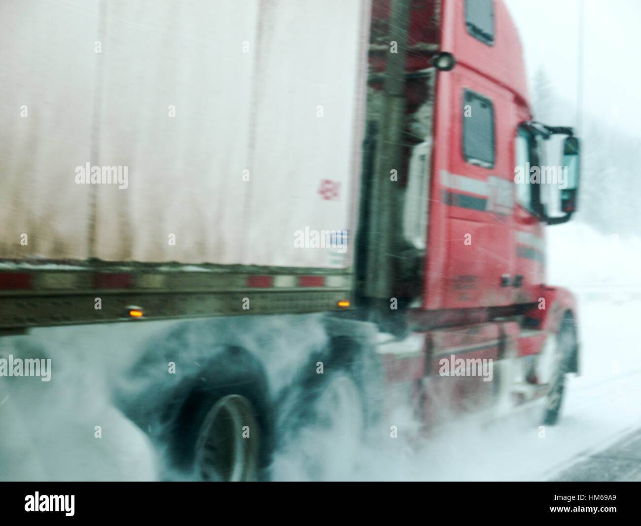 Pan motion blur of moving truck in snow storm on Trans-Canada Highway near Golden; British Columbia; Canada - Stock Image