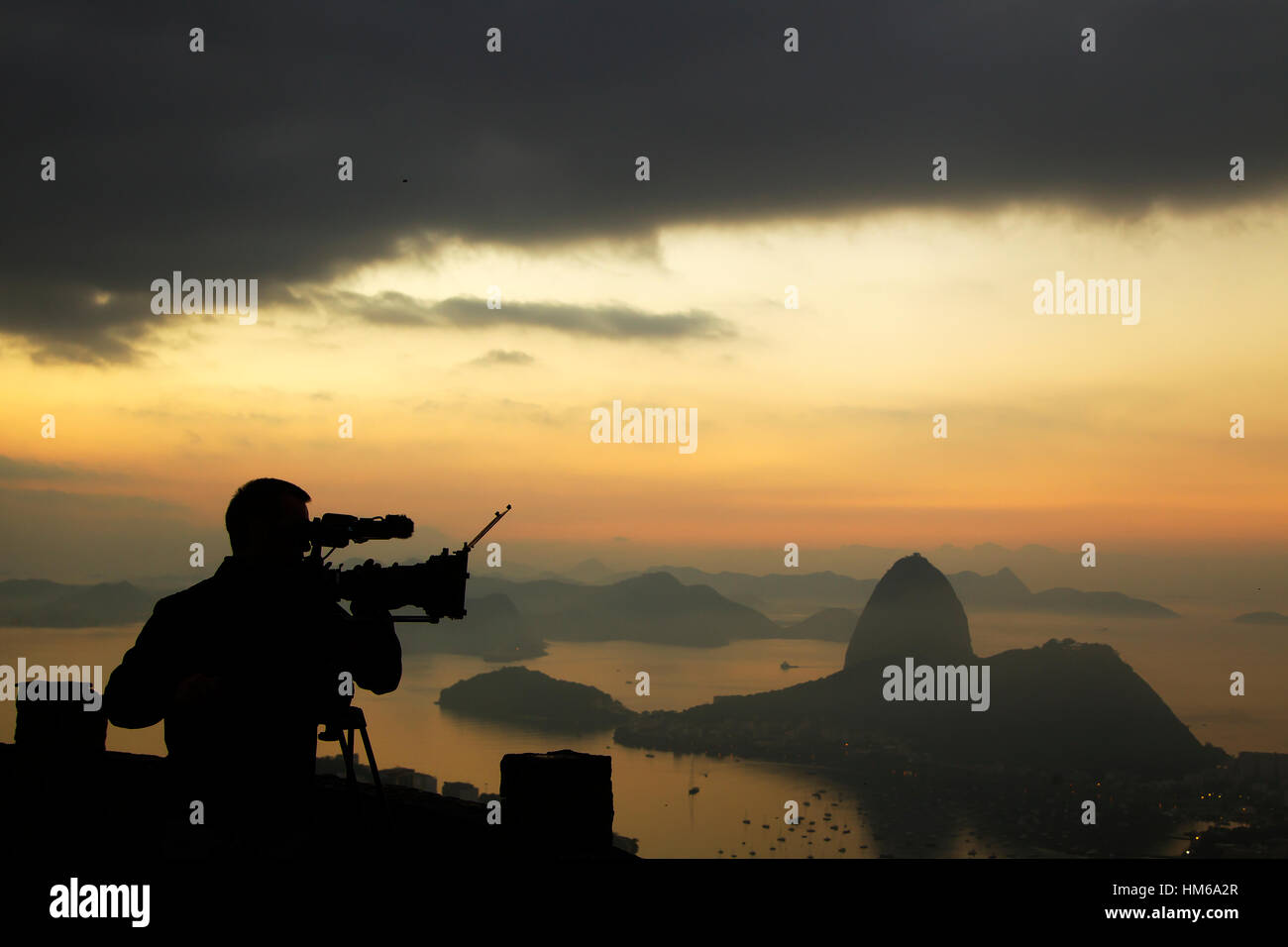 Cameramen filming the sunrise from Dona Marta Lookout with sugarloaf in the background, Rio de Janeiro, Brazil - Stock Image