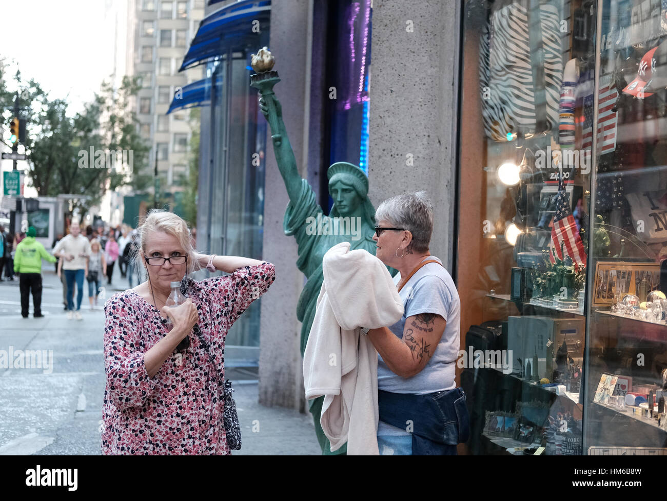 Senior women seen outside a souvenir shop in central New York City, looking at the camera. - Stock Image