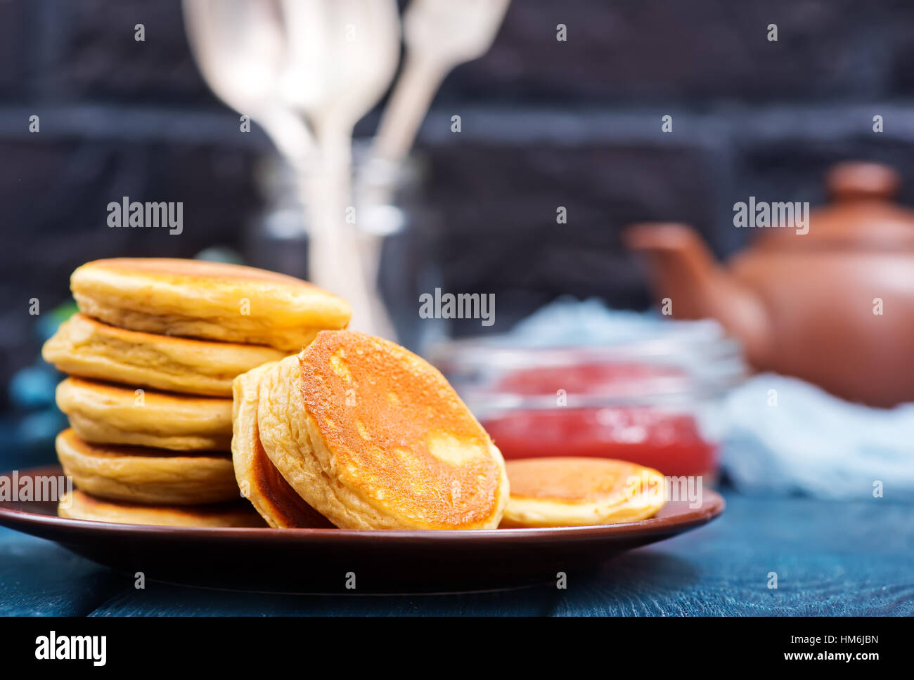 fresh pancakes on plate and on a table - Stock Image
