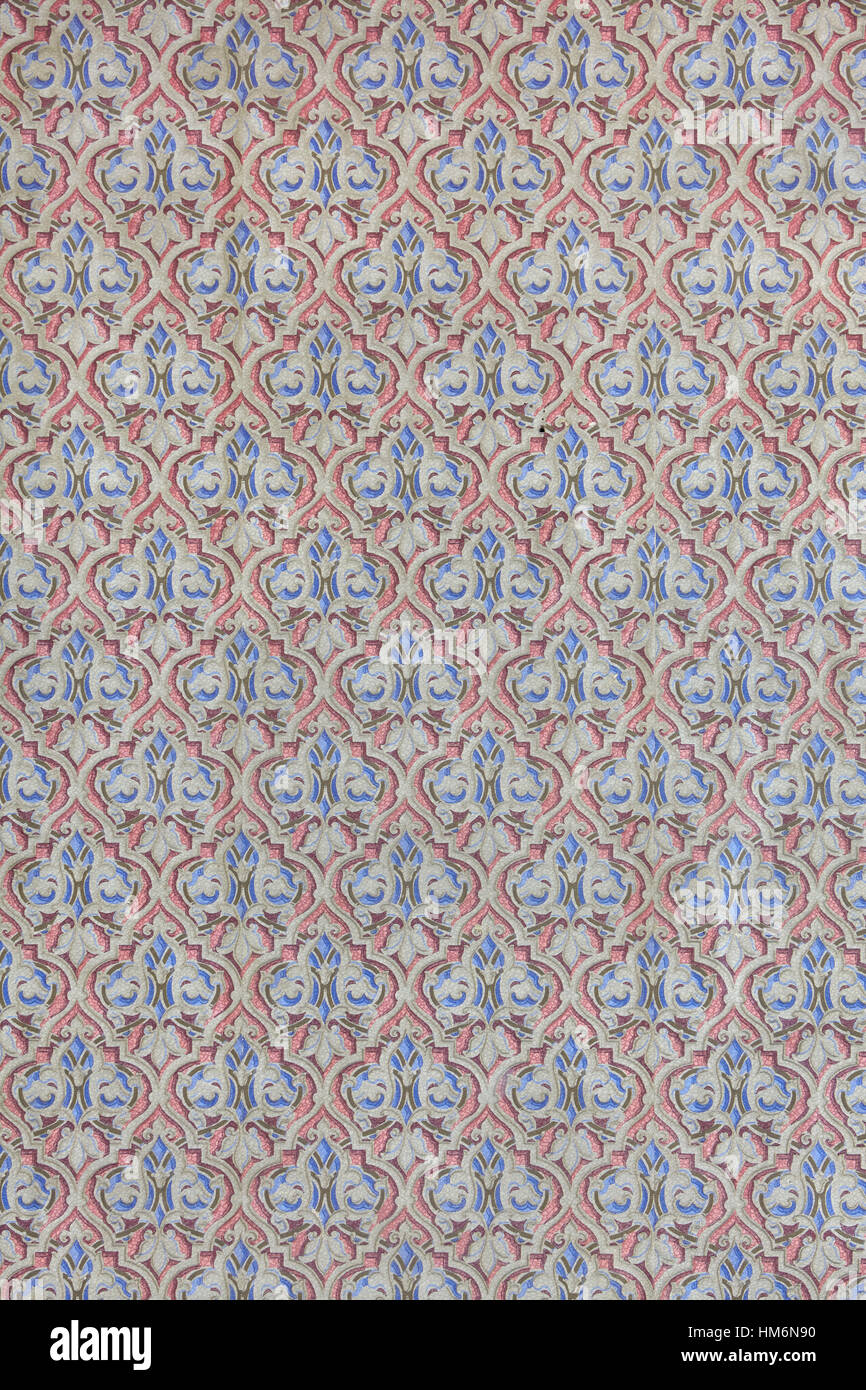 old wallpaper with baroque and antique pattern in the form of lilies, blue and red background - Stock Image
