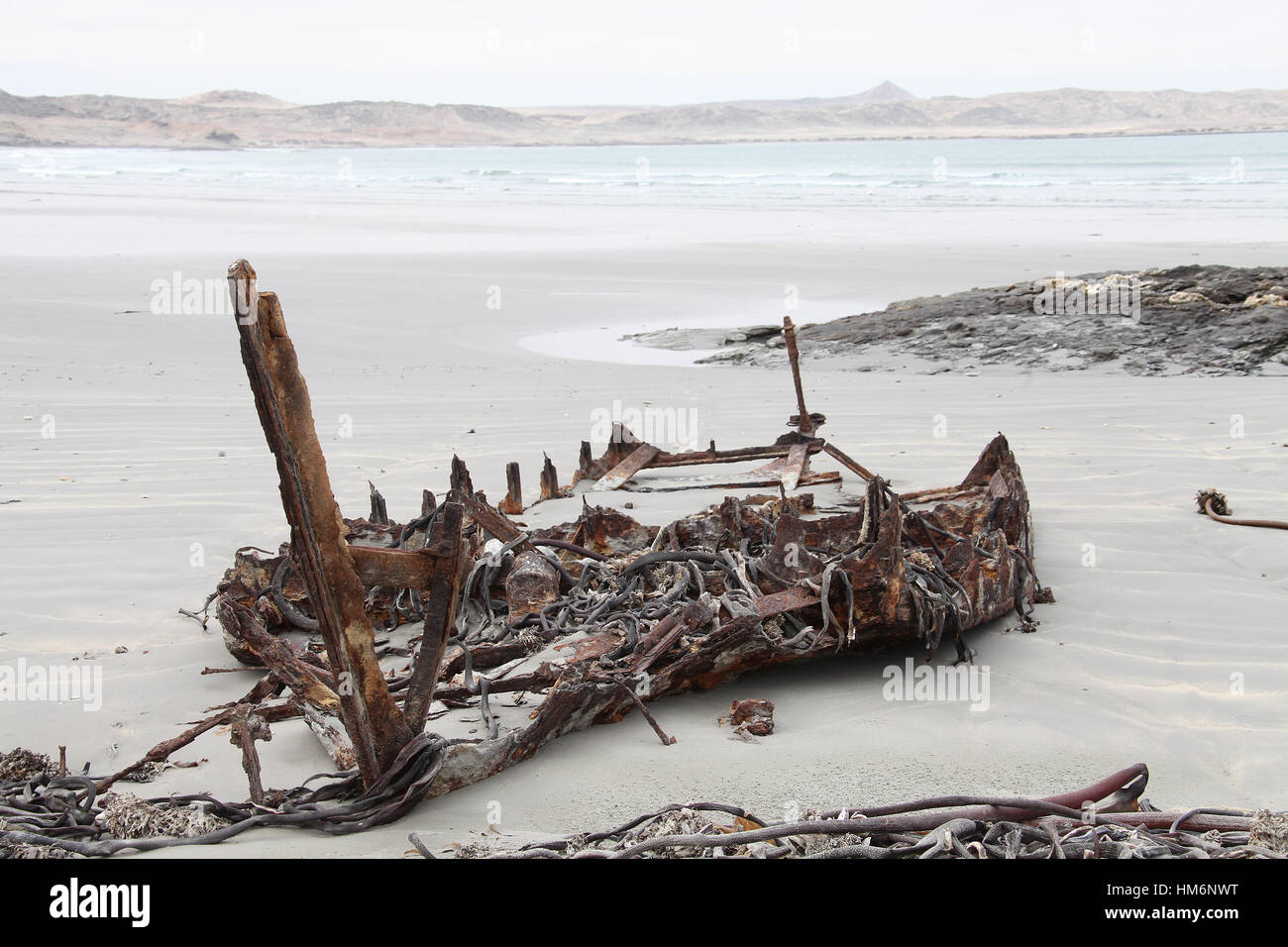 Remains of a boat on the beach at Grosse Bucht on the Luderitz Peninsula in Namibia - Stock Image