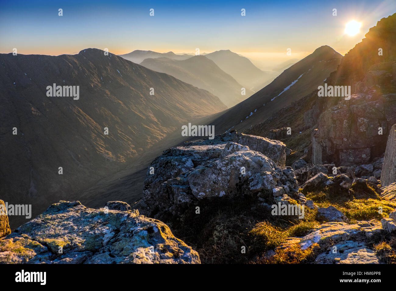 Setting sun and view down Geln Etive from Buchaille Etive Beag, Scottish Highlands - Stock Image