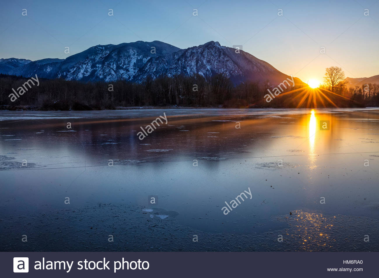 The sun's rays stretch across the frozen Borst Lake as the sun rises alongside Mount Si, a 4167-foot (1270-meter) - Stock Image