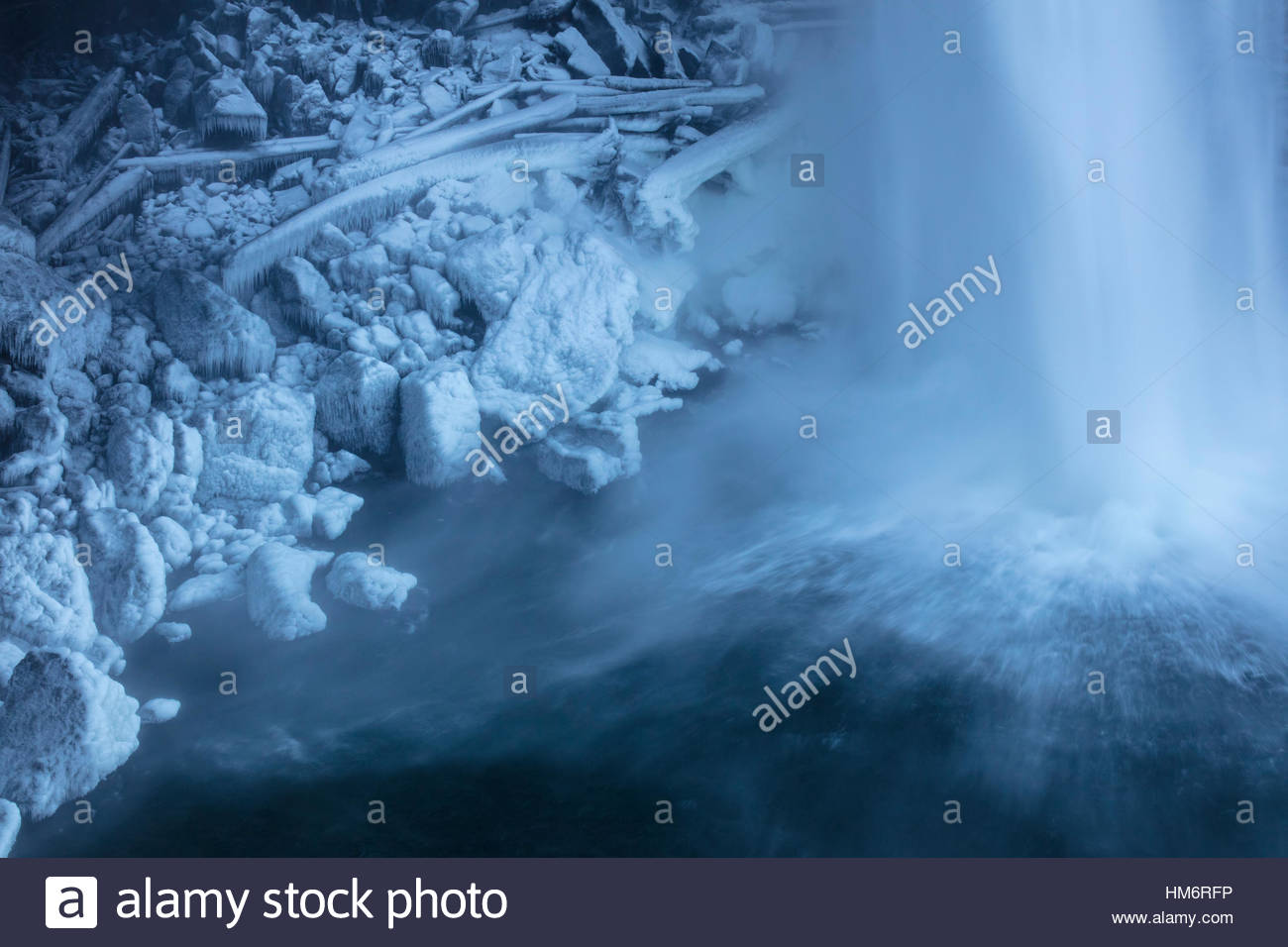 Spray from Snoqualmie Falls, located near Snoqualmie, Washington, freezes to rocks and logs at the base of the waterfall - Stock Image