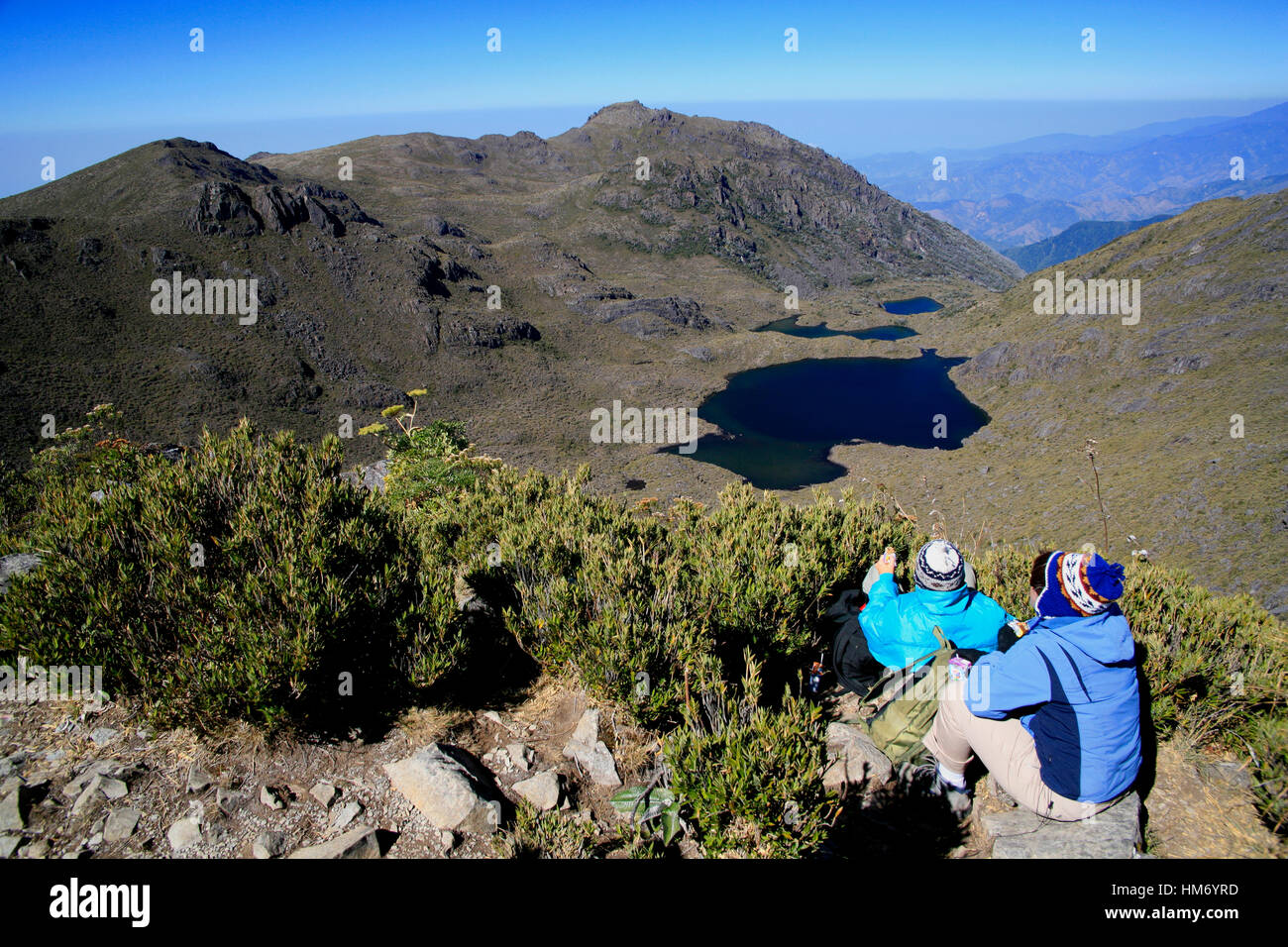 Tourists looking at Lake Chirripo from the summit of Mount Chirripo, Costa Rica's highest mountain (3820m). - Stock Image