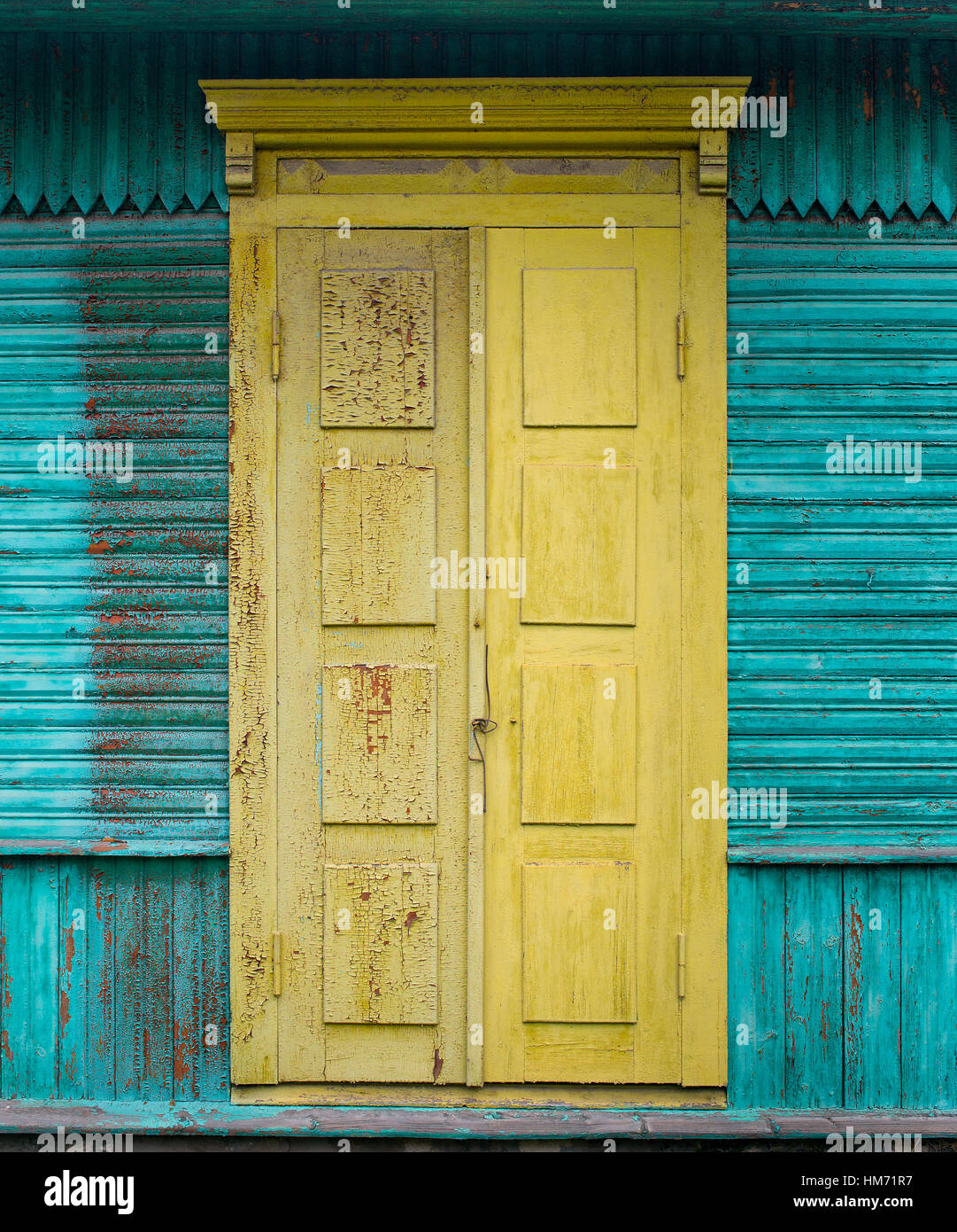 Yellow entrance door of the old wooden house which walls are painted ...