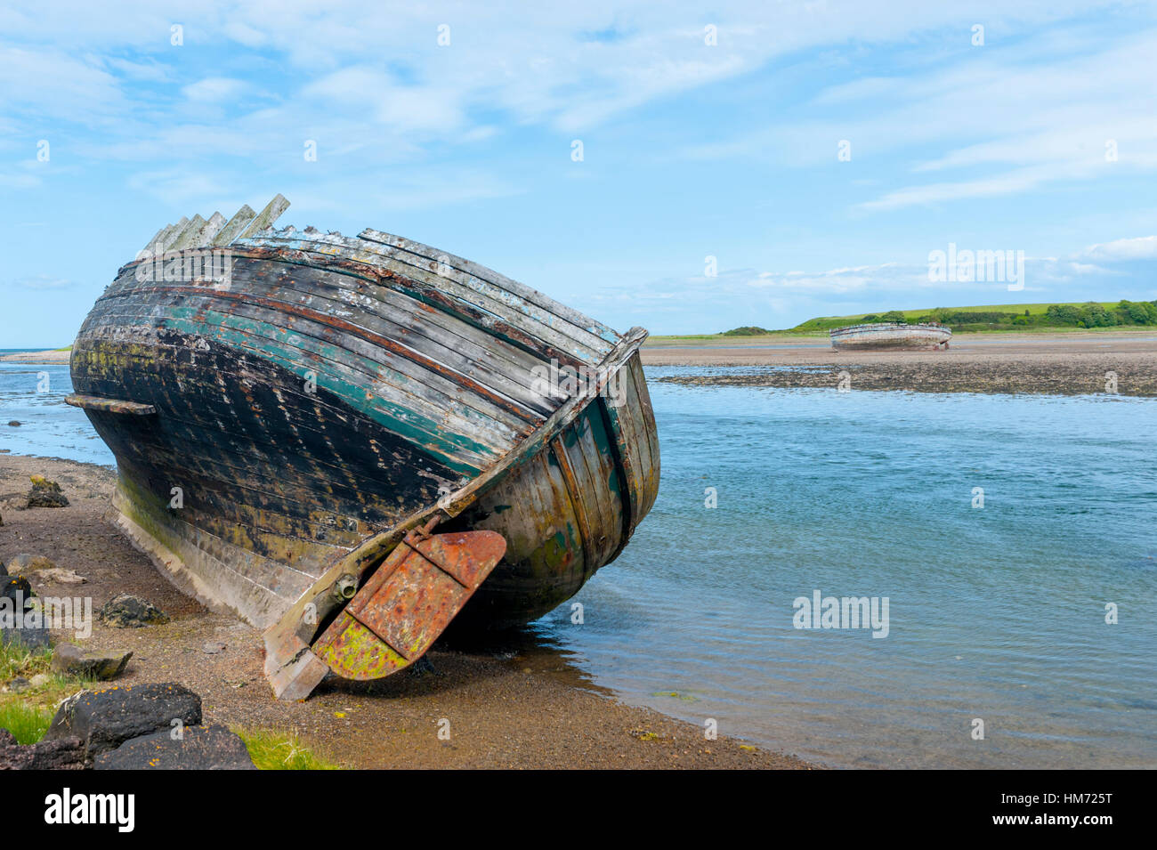 Wrecked boats aground on mud banks at Treath Dulas, Anglesey, Wales - Stock Image