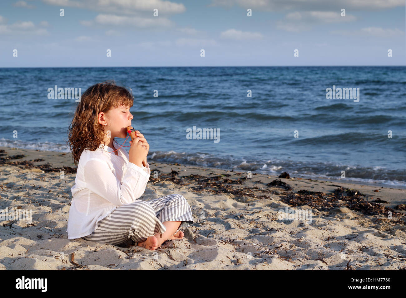 little girl play pan pipe on beach - Stock Image