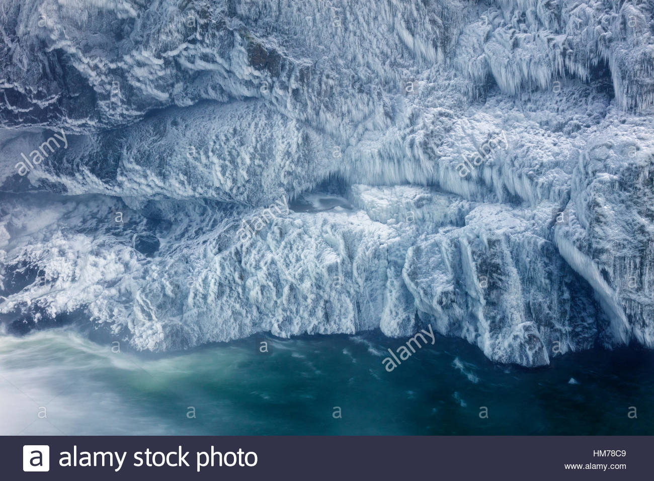 Spray from Snoqualmie Falls, located near Snoqualmie, Washington, freezes to the walls of the gorge downstream on - Stock Image