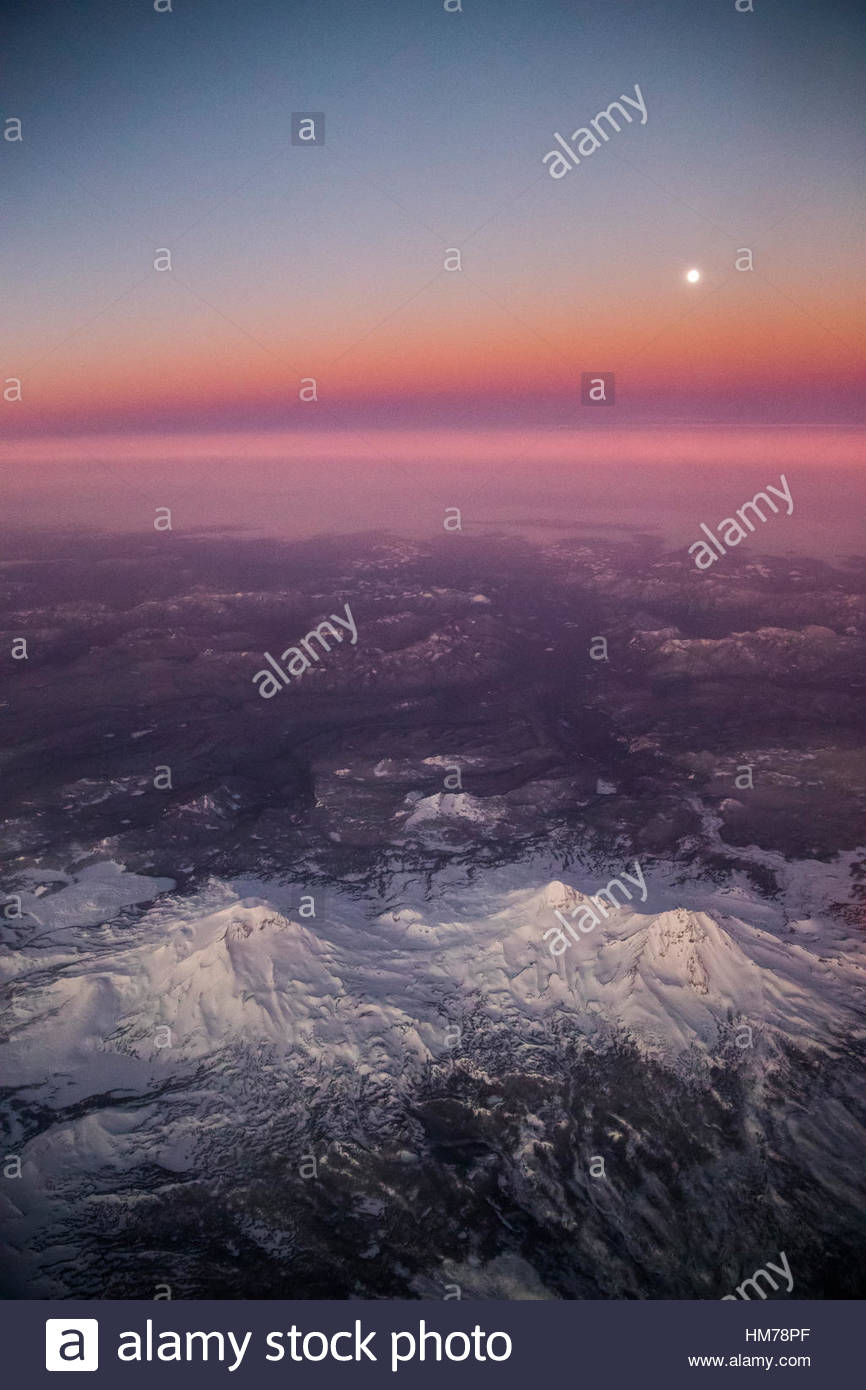 The Three Sisters, a cluster of three volcanic peaks in central Oregon, are bathed in alpenglow as the full moon - Stock Image