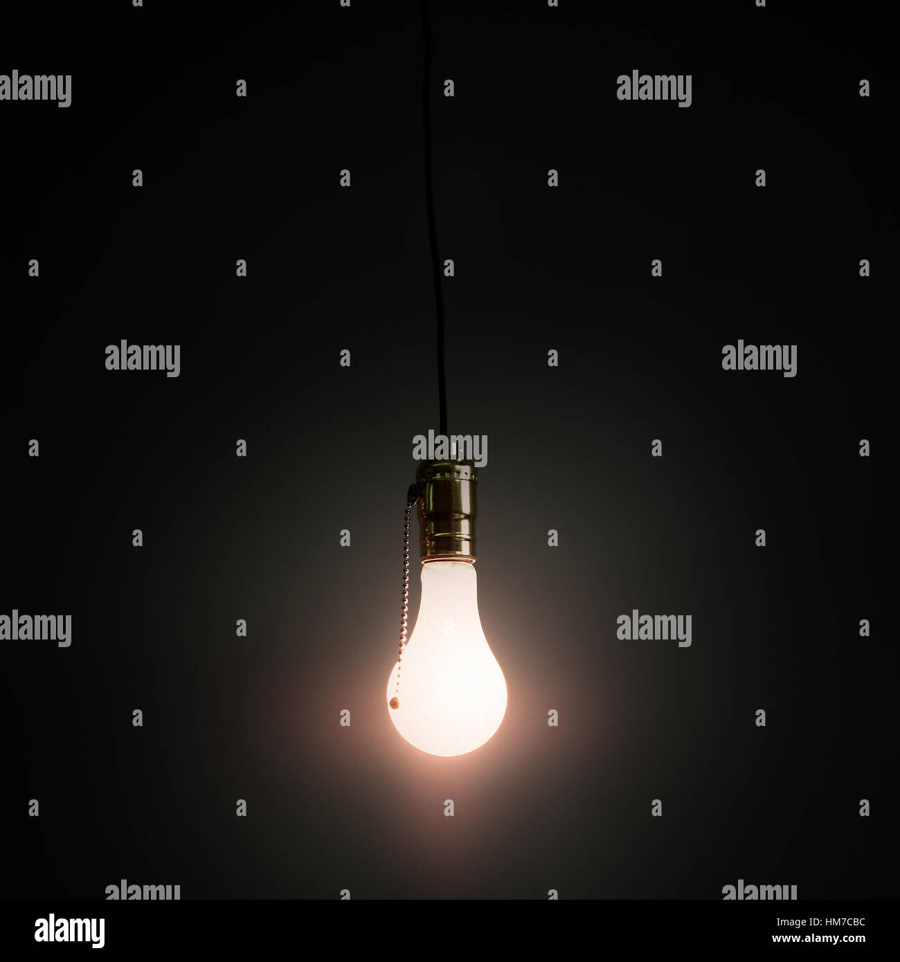 Light bulb hanging against grey background - Stock Image