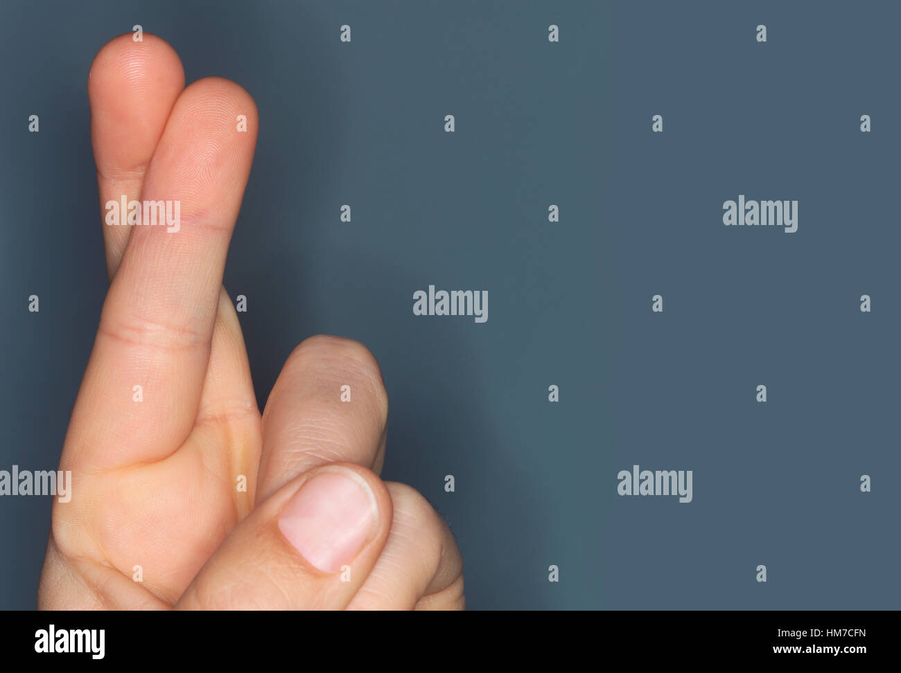 Close-up of hand with fingers crossed - Stock Image