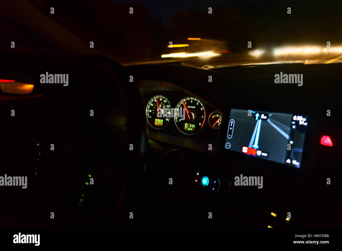 Dashboard of car on highway at night - Stock Image