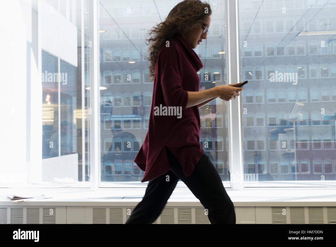 Young woman walking with mobile phone in front of window - Stock Image