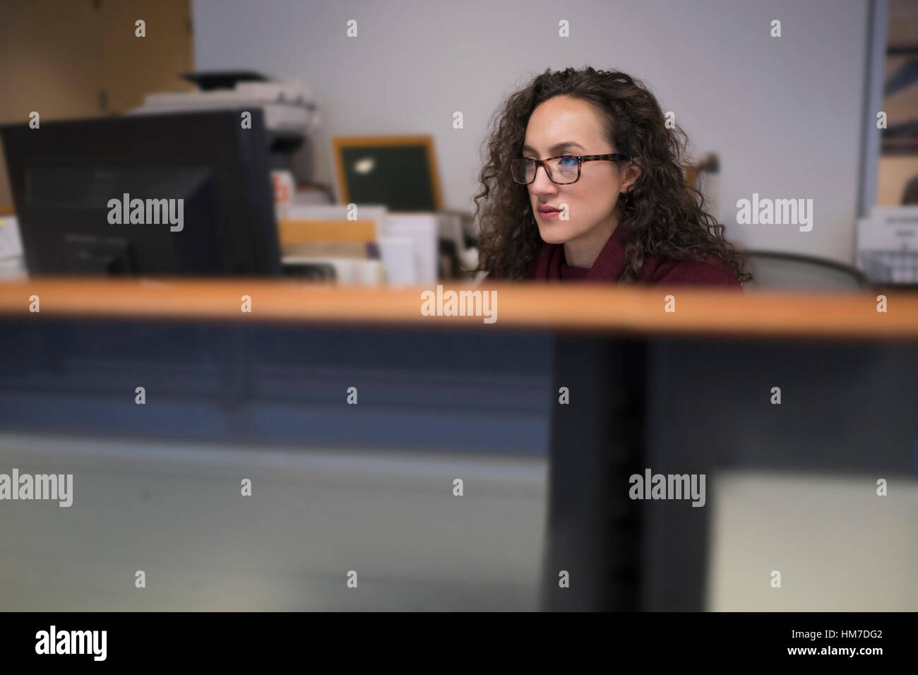 Young woman looking at computer monitor - Stock Image