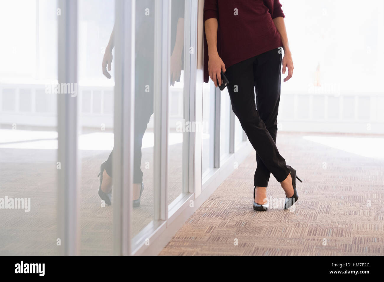 Low section of young woman leaning on glass wall - Stock Image