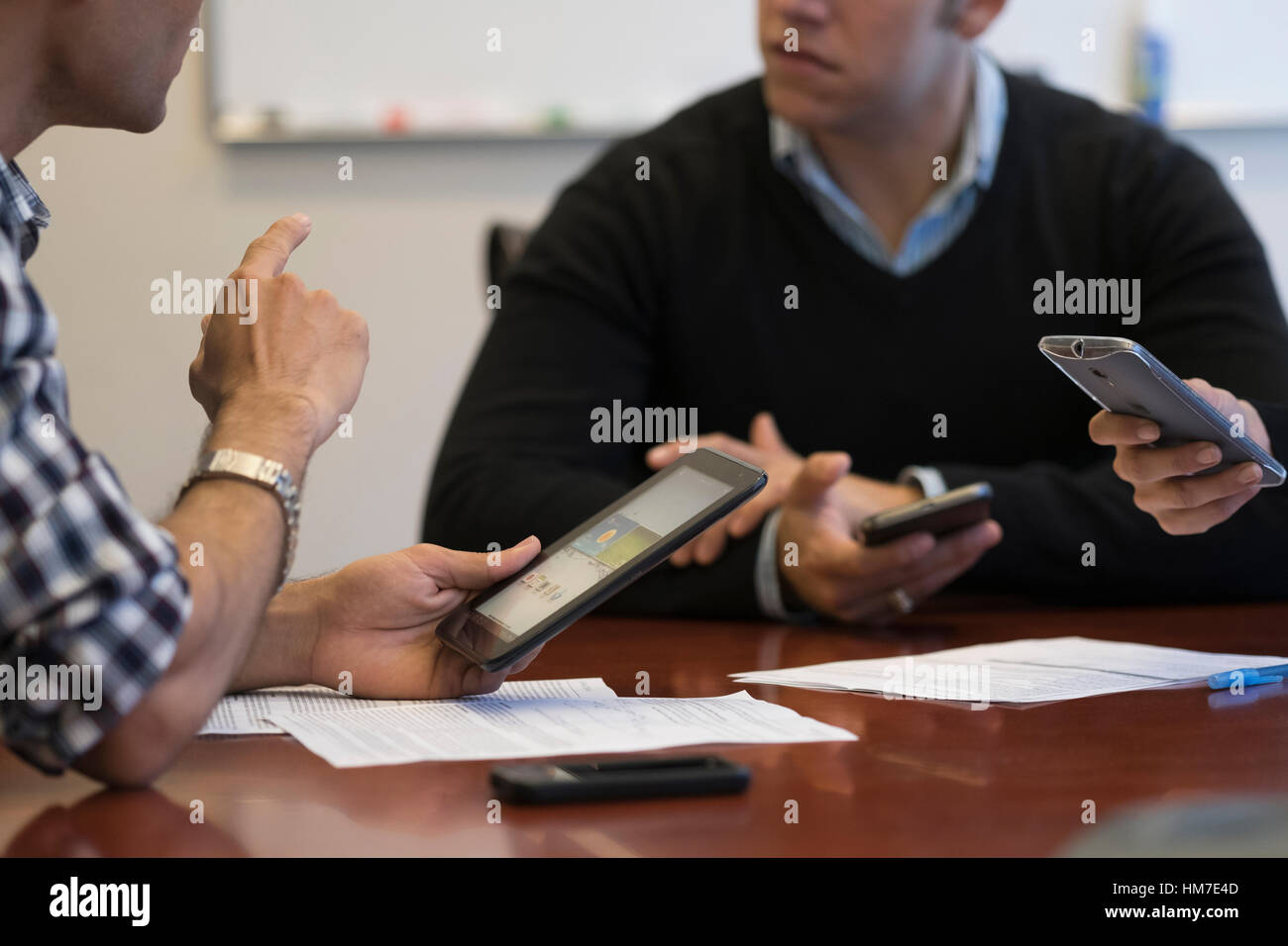 Mid section of business people using mobile devices - Stock Image