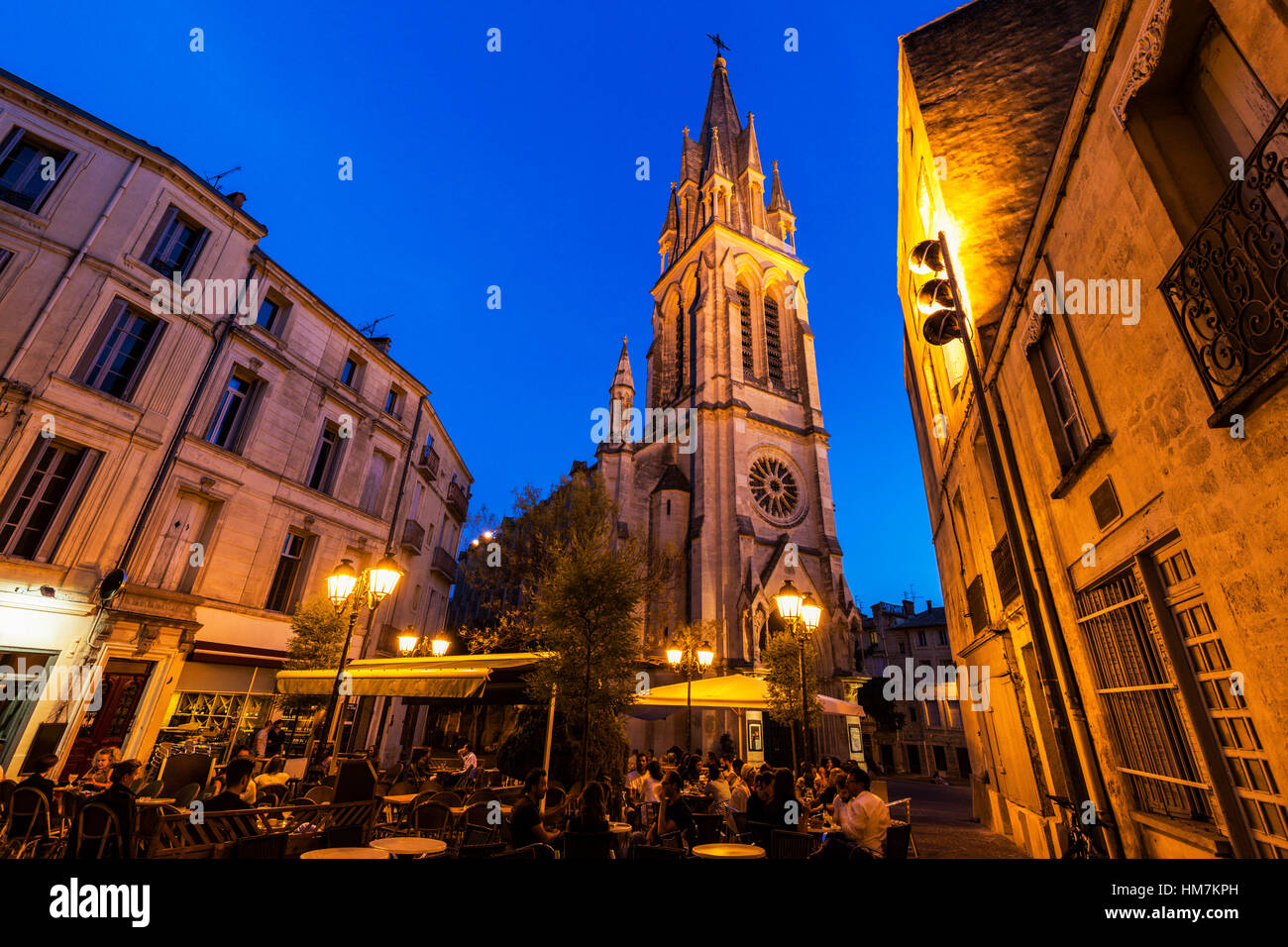 France, Occitanie, Montpellier, Sidewalk cafe and St. Anne Church at dusk - Stock Image