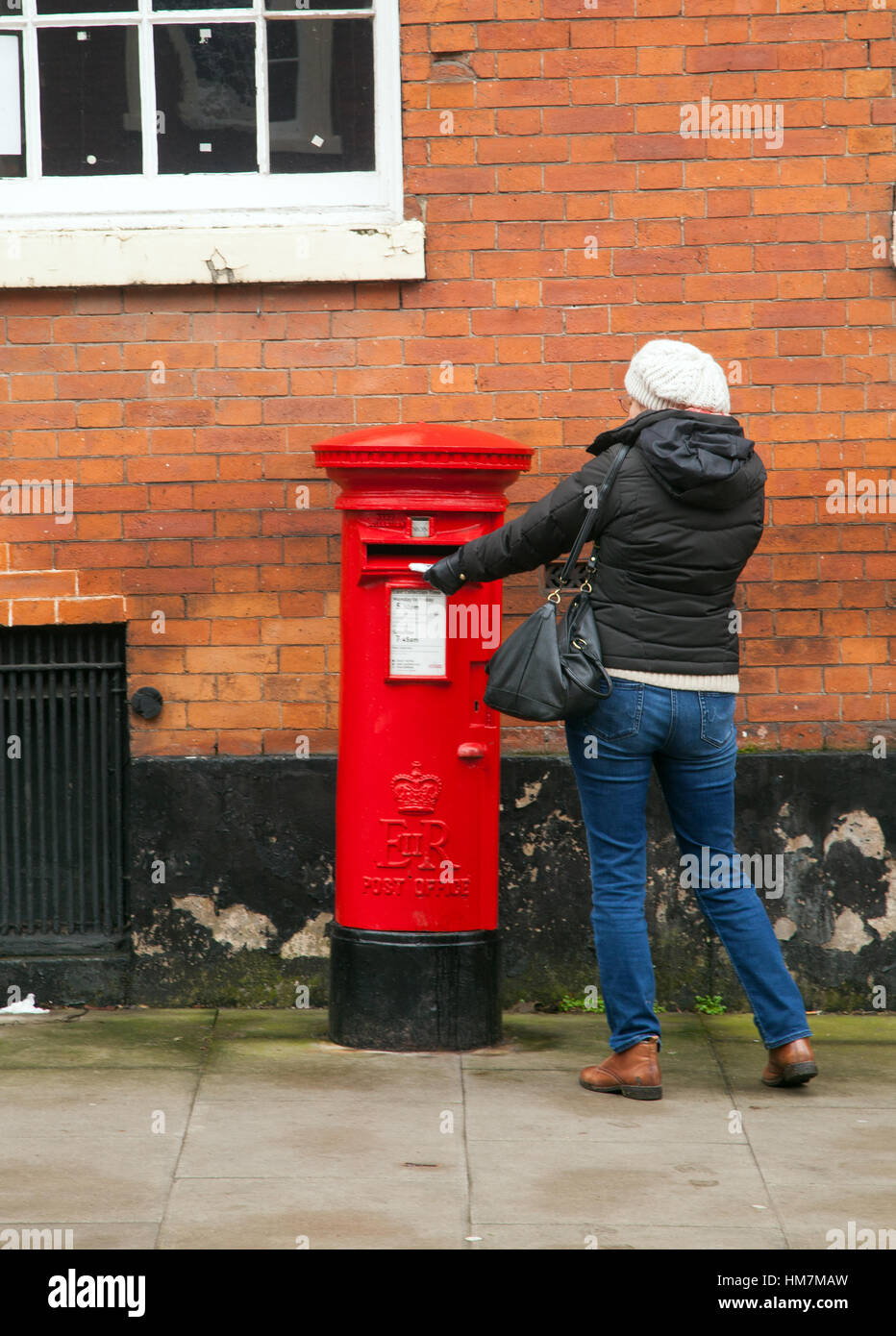 Woman posting a letter in a round red post box - Stock Image