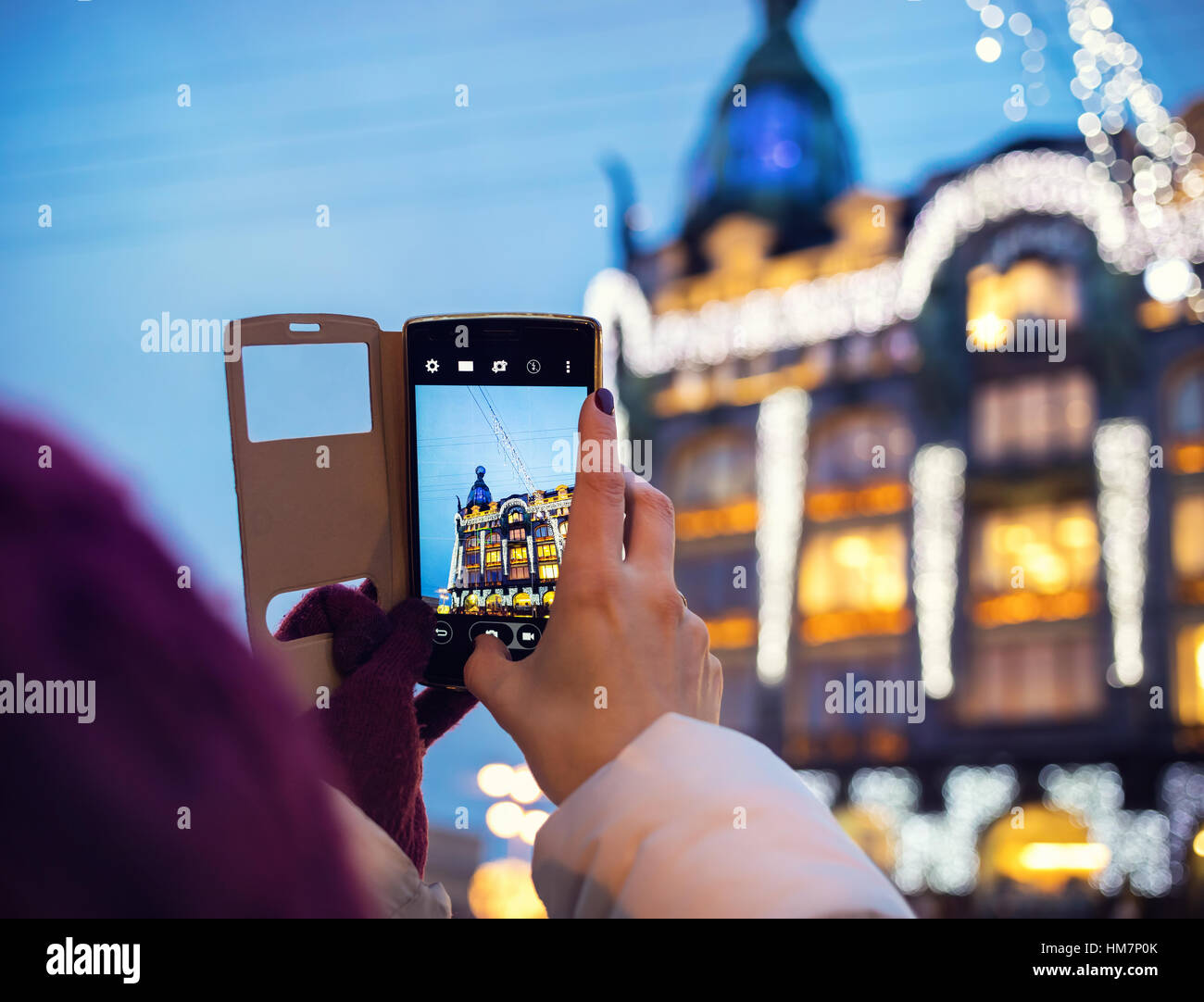 Woman taking pictures of Book Home Zinger Building by her Smartphone in Saint Petersburg Stock Photo
