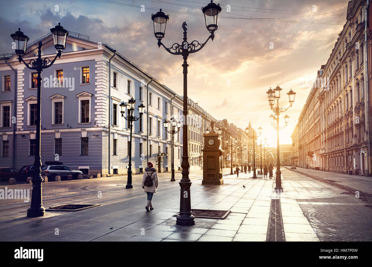 Woman in white jacket walking Malaya Konyushennaya  street with Lanterns and ol buildings in Saint Petersburg - Stock Image