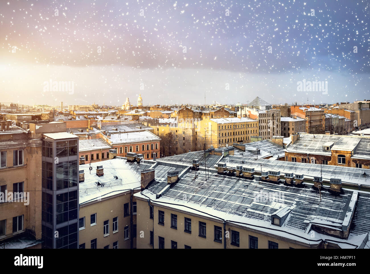 Panoramic view old buildings from the roof at snow fall at sunset in Saint Petersburg, Russia - Stock Image