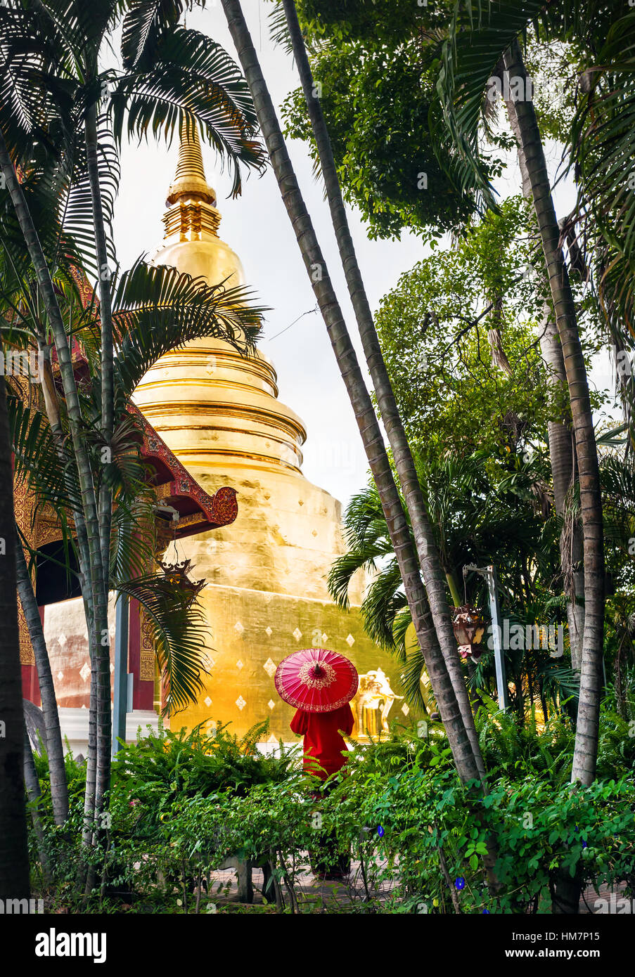 Woman tourist with red traditional Thai umbrella near Golden Stupa at temple Wat Phra Singh near bamboo tropical - Stock Image