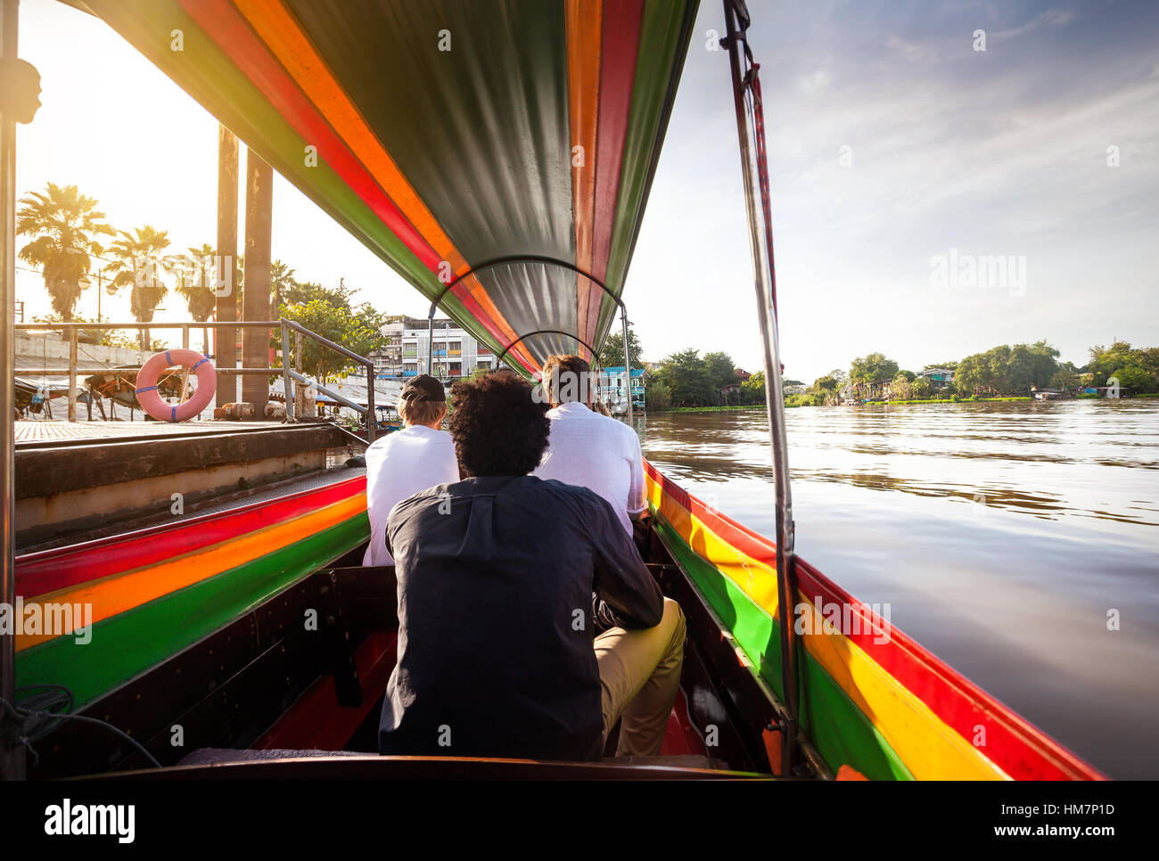 Tourist sitting in long-tail boat cruise by Chao Phraya river in Ancient city Ayutthaya at Sunset, Thailand Stock Photo