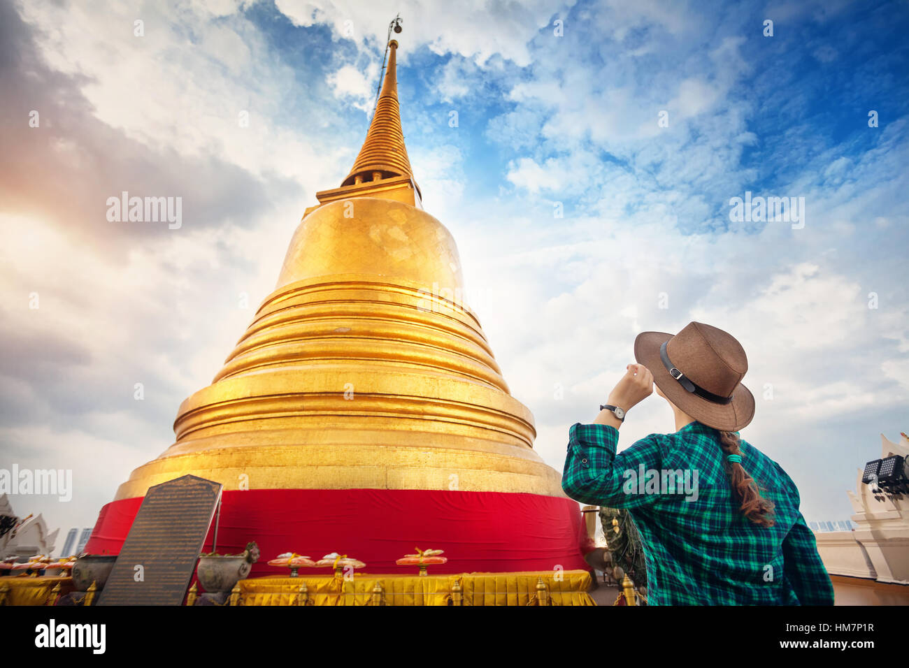 Tourist woman in hat and green checked shirt looking at big golden Stupa in Wat Saket temple in Bangkok, Thailand - Stock Image