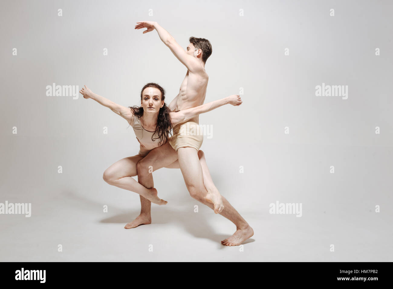 Inventive young dancers performing in the white colored studio - Stock Image