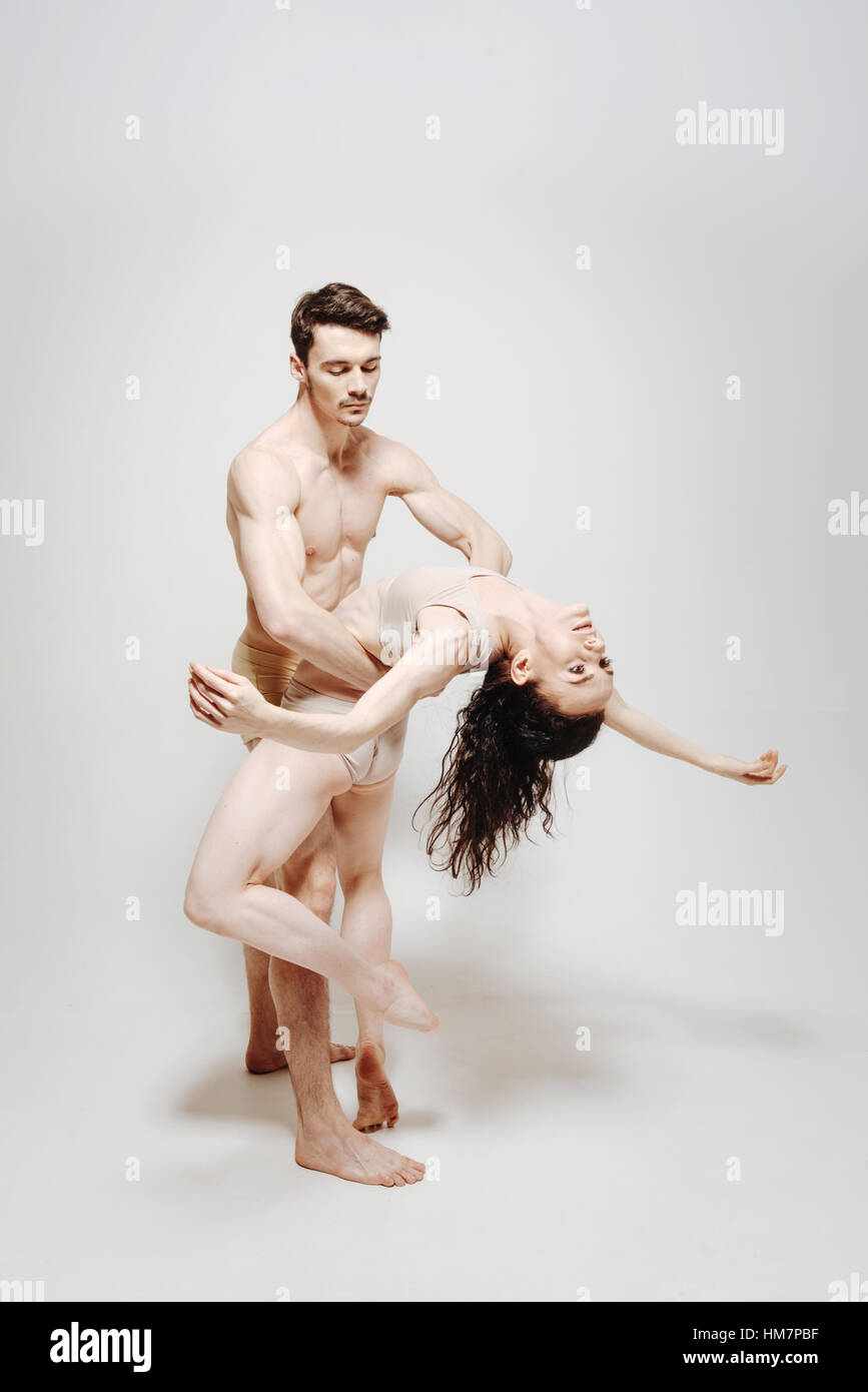 Skillful dancers performing in front of the white background - Stock Image