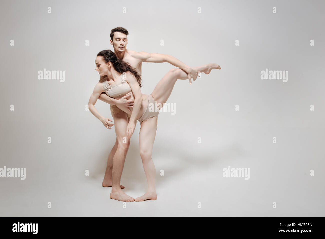 Young couple stretching isolated in white background - Stock Image