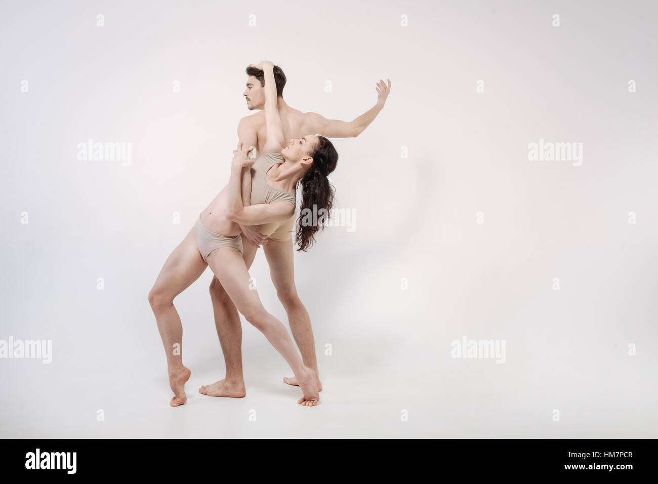 Amusing young gymnasts dancing in the white colored studio - Stock Image