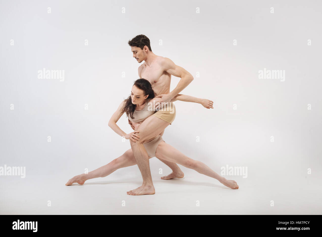 Active young gymnasts showing their choreography in the studio - Stock Image