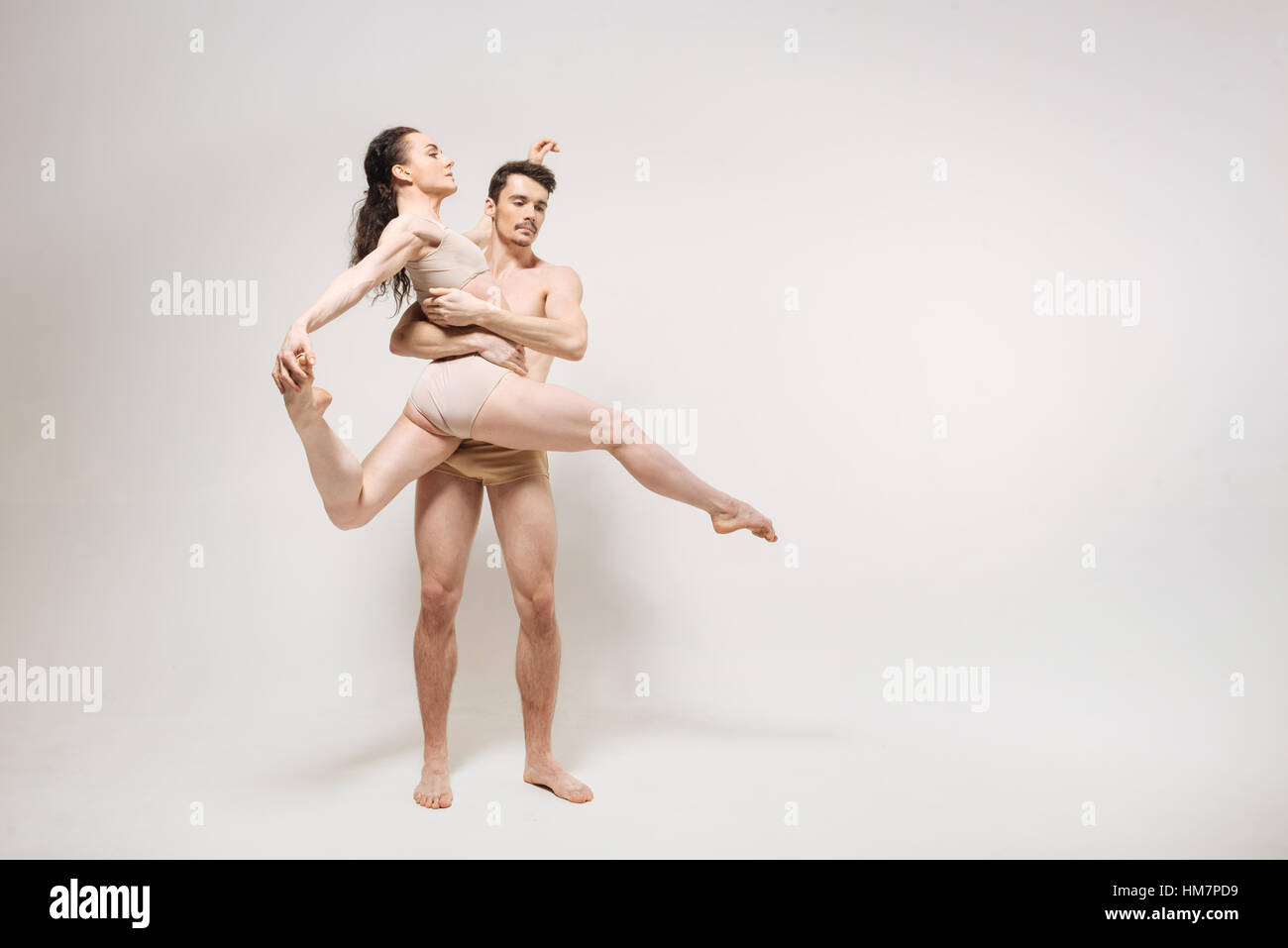 Proficient young ballet dancers performing in the white room - Stock Image