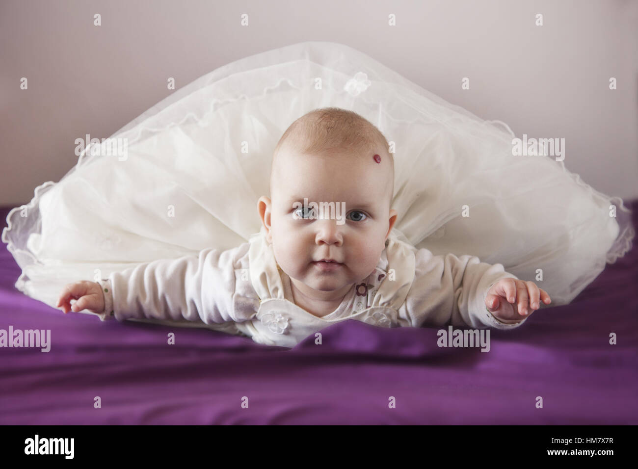 Portrait of baby boy (18-23 months) lying on bed - Stock Image