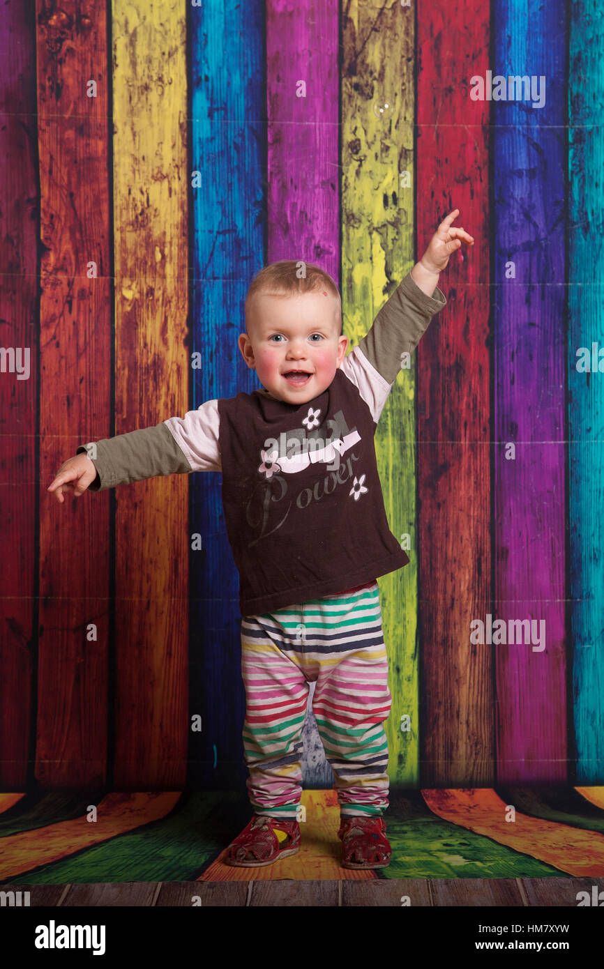 Baby kid in front of color full background showing up with her hands. - Stock Image