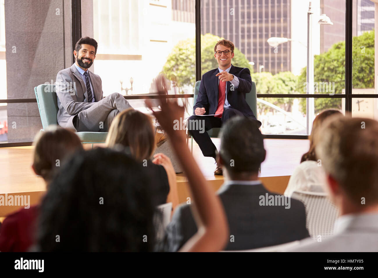 Speakers at a business seminar take questions from audience - Stock Image