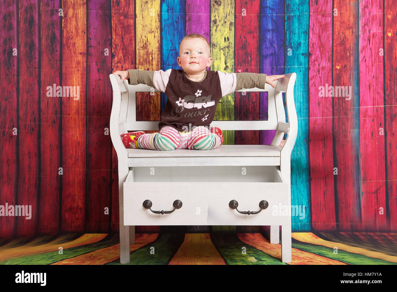 Portrait of baby girl sitting on Thon Thonnet chair in front of color full background - Stock Image