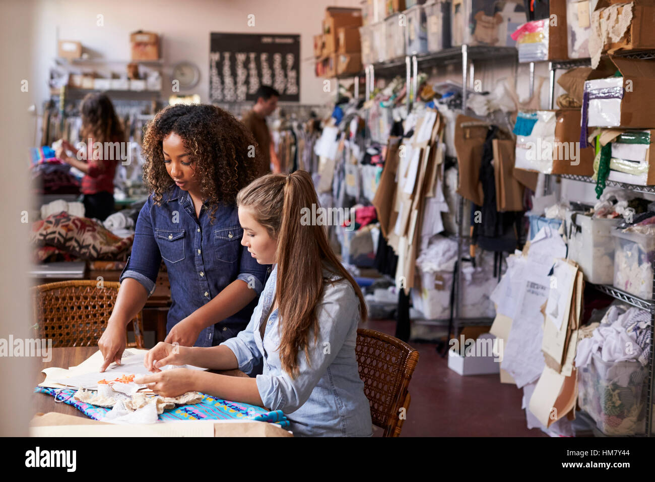 Woman stands to train an apprentice at clothes design studio - Stock Image